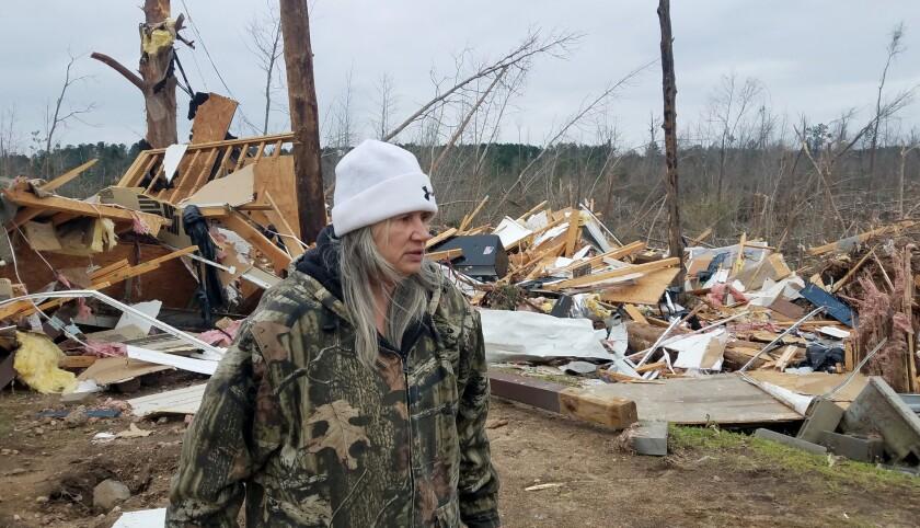 Julie Morrison looks at the debris of her destroyed home on Lee County Road 63 in Beauregard, Ala.,