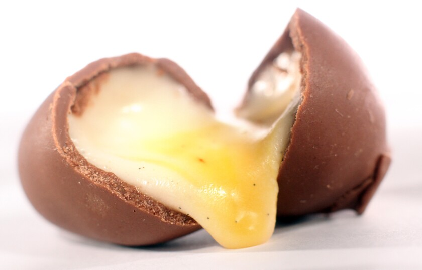 Cream filling drips from a homemade chocolate Easter egg.