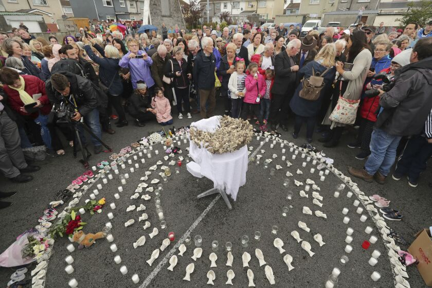 """FILE - In this Aug. 26, 2018 file photo, People gather to protest at the site of the former Tuam home for unmarried mothers in County Galway, Ireland. The Vatican has indicated its support for a campaign to exhume the bodies of hundreds of babies who were buried on the grounds of a Catholic-run Irish home for unwed mothers to give them a proper Christian burial. The Vatican's ambassador to Ireland, Archbishop Jude Thaddeus Okolo, said in a July 15, 2020 letter to the amateur Irish historian behind the campaign that he shared the views of the archbishop of Tuam, Ireland, Michael Neary, who has said it was a """"priority"""" for him to re-inter the bodies in consecrated ground. (Niall Carson/PA via AP, file)"""