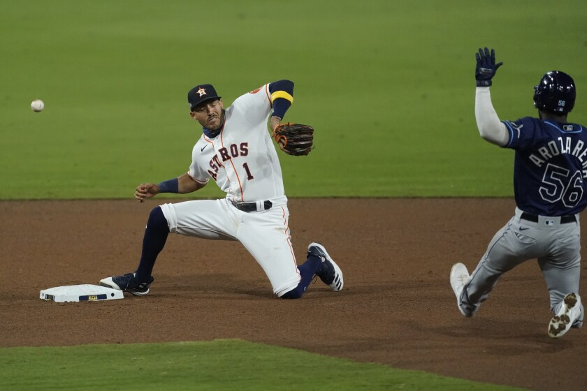 Houston shortstop Carlos Correa misses a throw from Jose Altuve, allowing Tampa Bay's Randy Arozarena to be safe at second.
