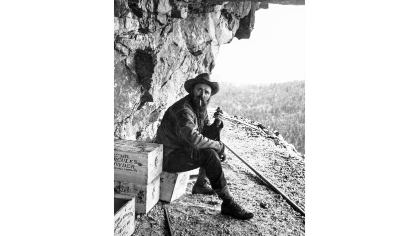 Polish American sculptor Korczak Ziolkowski (1908-82) smokes near a crate of dynamite, high up on a bluff of the Black Hills, 1950. Having assisted in the carving of Mt. Rushmore, he worked on the Crazy Horse Memorial at the request of the Lakota people.