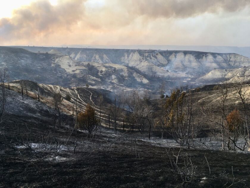 A wildfire smolders near the Burning Hills Amphitheatre Thursday, April 1, 2021 near Medora, N.D. Officials say firefighters have stopped a wildfire from spreading in the western North Dakota tourist town of Medora, where its 100 residents were forced to evacuate. (Tom Stromme/The Bismarck Tribune via AP)