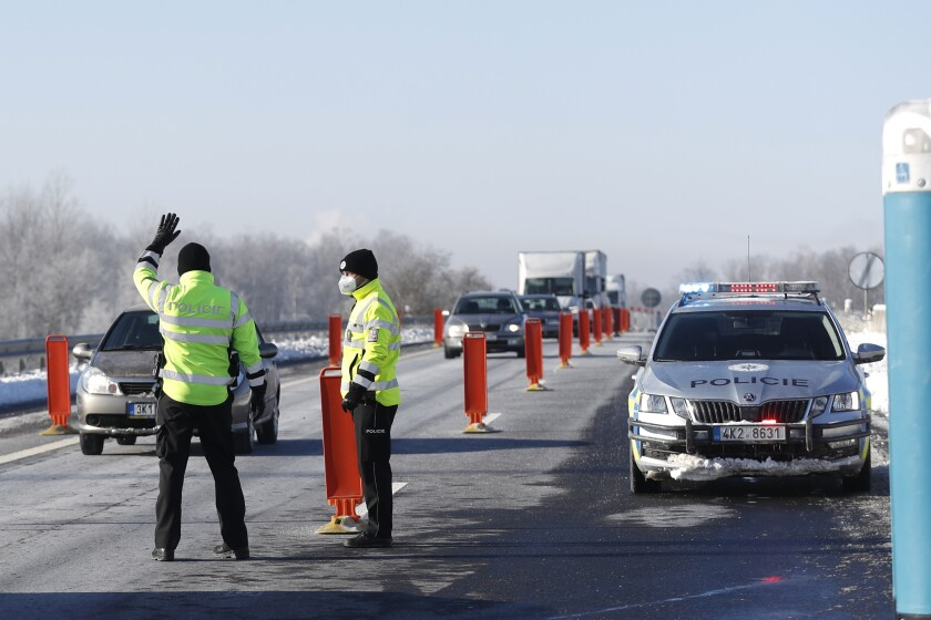 Policemen stop a car to check documents of a driver near the city of Sokolov, Czech Republic, Friday, Feb. 12, 2021. Almost 600 police officers were deployed to enforce a complete lockdown of the three hardest-hit counties on the border with Germany and Poland to help contain a fast-spreading variant of the coronavirus found in Britain. (AP Photo/Petr David Josek)