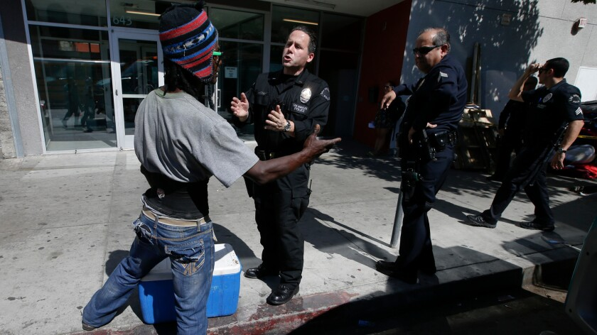 Los Angeles police officers talk to a homeless man on San Pedro Street along skid row.
