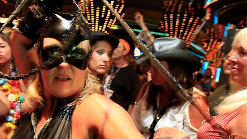 Catwoman joins the crowd during costume dance party aboard a Carnival ship. The line got high marks from dads, moms and bargain shoppers.