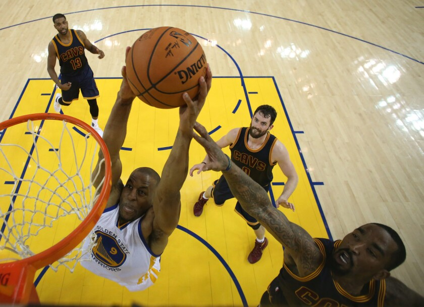 Cavaliers forward J.R. Smith, right tries to block the dunk attempt of Warriors' Andre Iguodala, left, during the first half.