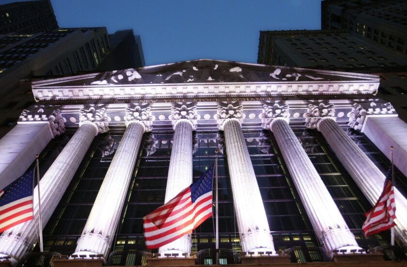 FILE - In this Wednesday, Oct. 8, 2014 file photo, American flags fly in front of the New York Stock Exchange, in New York.  Global stock markets turned lower on Friday, Feb. 19, 2016 on lingering concerns about the slump in oil prices and uncertain prospects for the global economy. (AP Photo/Mark
