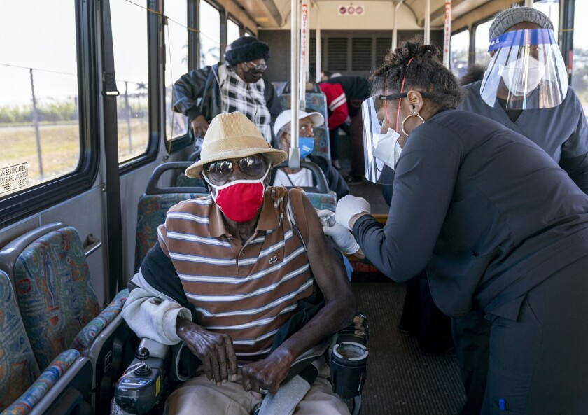 FILE - In this Feb. 3, 2021, file photo, a senior receives a COVID-19 vaccine from a healthcare worker after arriving on a bus to a vaccination site at Anquan Boldin Stadium in Pahokee, Fla. About three-quarters of all first-dose shots in Florida have gone to those 65 years or older. (Greg Lovett/The Palm Beach Post via AP, File)