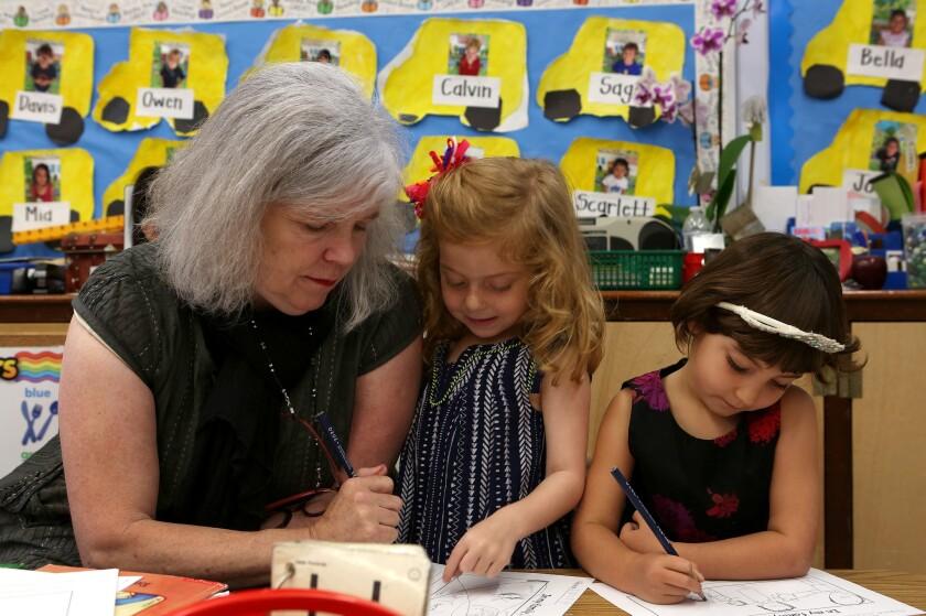Missy Morris helps students  Emma Jean de Souza  and Jesse Rhoden, in her kindergarten classroom.
