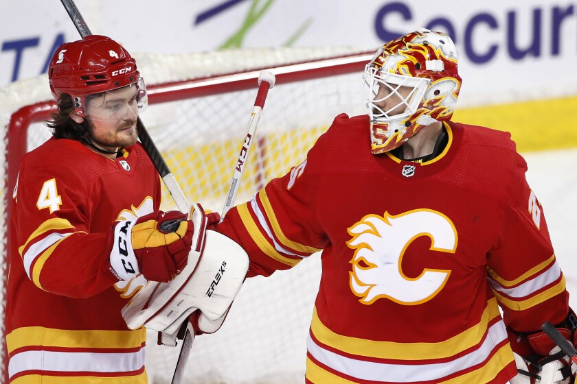 Calgary Flames goalie Jacob Markstrom, right, is congratulated by Rasmus Andersson after the team's 6-1 victory over the Ottawa Senators in an NHL hockey game Sunday, May 9, 2021, in Calgary, Alberta. (Larry MacDougal/The Canadian Press via AP)