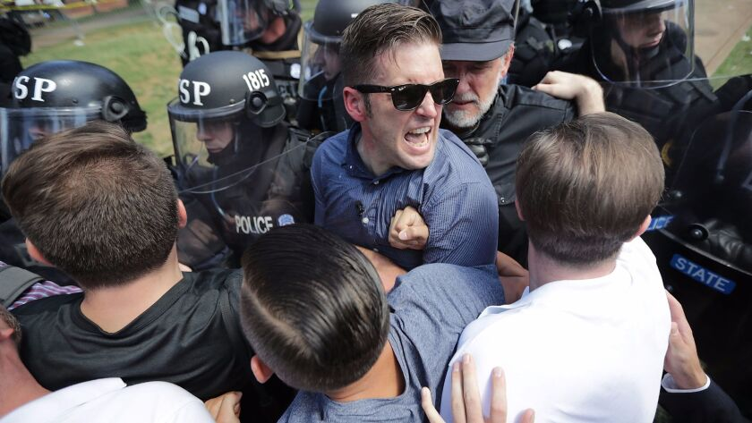 "White nationalist Richard Spencer, in sunglasses, and his supporters clash with Virginia State Police in Lee Park after the ""Unite the Right"" rally was declared an unlawful gathering Aug. 12 in Charlottesville."