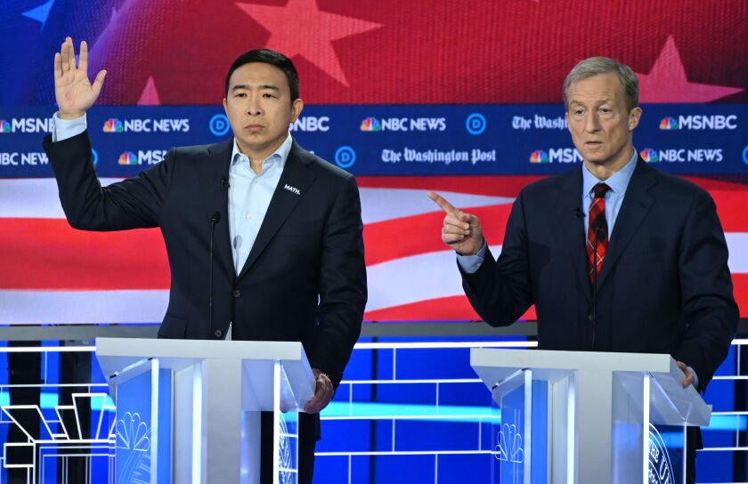 Andrew Yang motions on Nov. 20 debate stage while Tom Steyer speaks.