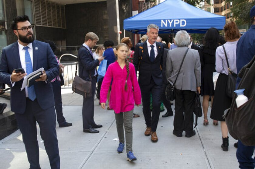 Environmental activist Greta Thunberg, center, of Sweden, walks with an entourage after passing a security checkpoint while appearing at the United Nations, Monday, Sept. 23, 2019 in New York.