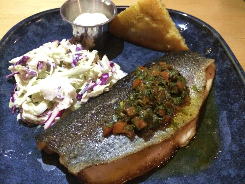 Campfire trout atop chimichurri, with coriander slaw and masa cornbread at One Door North.