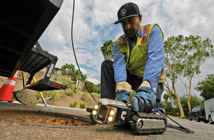 Hugo Gonzalez, a Leucadia Wastewater District technician, prepares a camera to search for roots in a Carlsbad, Calif., sewer line. Without normal levels of outdoor irrigation, tree roots in search of water have invaded sewer pipes and grown there over time.
