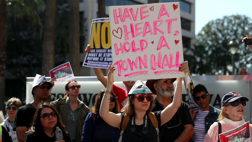 Protesters hold signs outside the Los Angeles office of California's U.S. Sen. Dianne Feinstein on Feb. 14 to demand she hold a town hall meeting.