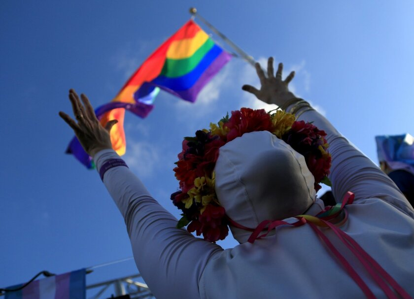 A member of the Sisters of Perpetual Indulgence waved her hands as the 30'x20' flag was raised during the Stonewall Rally at Normal Street and University Avenue in Hillcrest marking the start of festivities for Pride weekend on July 18, 2014.