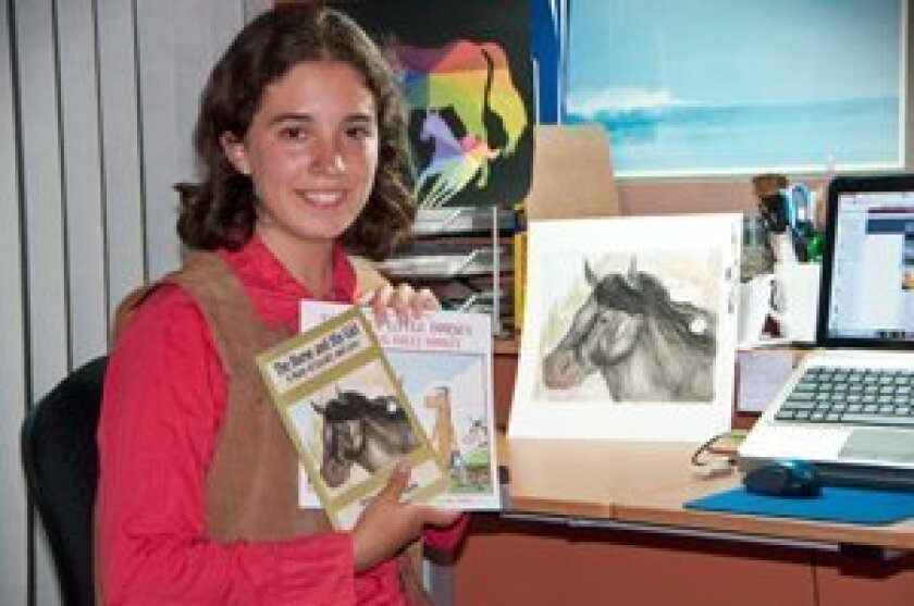 Liana-Melissa Allen sits at her workspace, where she creates her books and illustrations, as shown here. Photo/-Claire Harlin