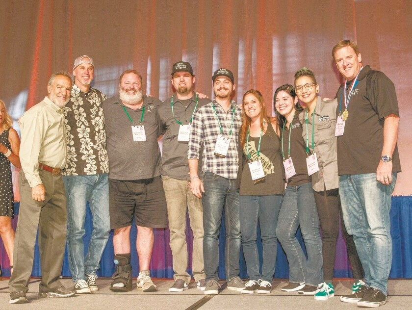 Karl Strauss Brewing employees celebrate their medal-winning beer at the 2017 Great American Beer Festival in Denver. Charlie Papazian, far left, is founder and past president of the Brewers Association, the annual competition's sponsor. MANDATORY CREDIT: Photo © 2017 Jason E. Kaplan