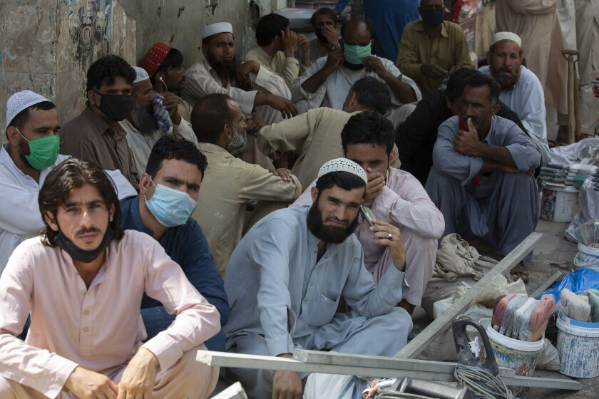 Unmasked laborers wait to be hired by customers in Rawalpindi, Pakistan, earlier this month.