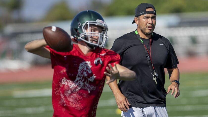 Costa Mesa's head coach David Gutierrez works with quarterback Blake Juncker during practice on Tues