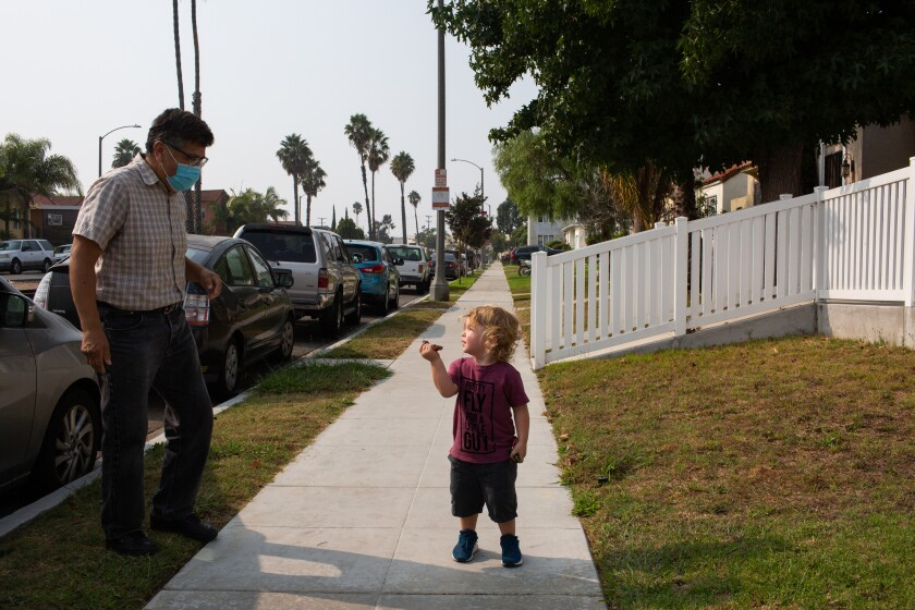 Abel Mata and his 2-year-old grandson play in the front yard of Mata's home in Torrance on Sept. 14.