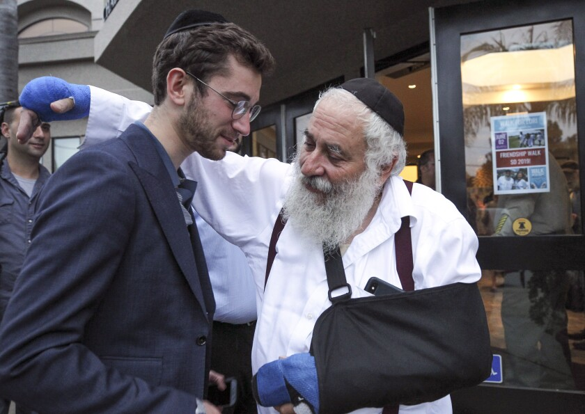 Rabbi Yisroel Goldstein, who was injured by the gunman that opened fire in the Chabad of Poway synagogue on April 27, puts his arm around Eric Ebert, a Canadian visitor to San Diego, just before they enter Chabad of Poway for a community meeting Wednesday. The forum was to help victims understand what resources are available to them.