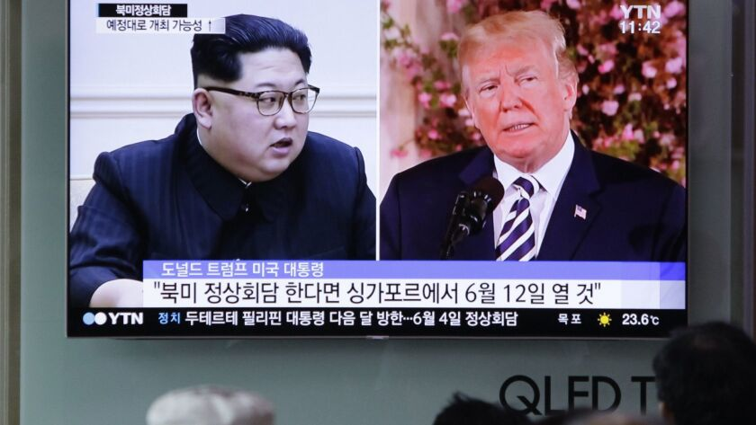People watch a TV screen on May 26 showing file footage of U.S. President Donald Trump and North Korean leader Kim Jong Un during a news program at the Seoul Railway Station in Seoul, South Korea.