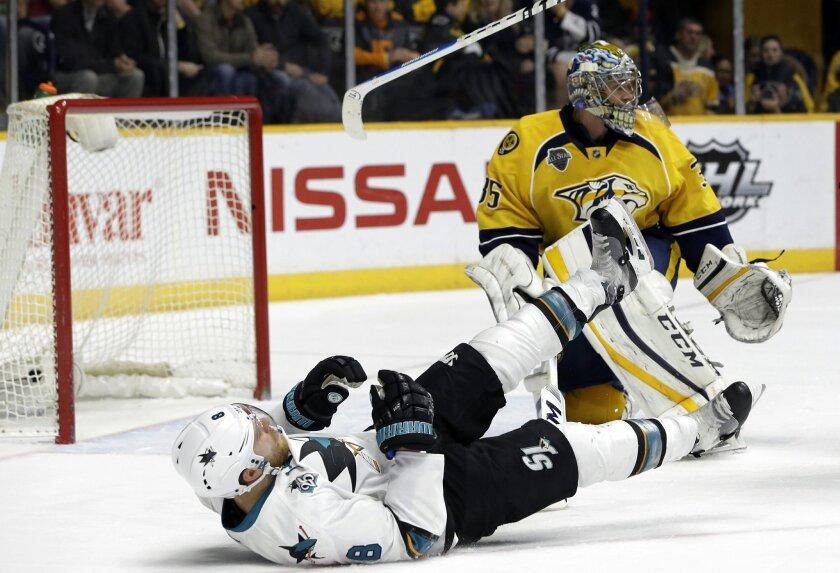 San Jose Sharks center Joe Pavelski (8) loses his stick as he falls in front of Nashville Predators goalie Pekka Rinne (35), of Finland, during the third period of an NHL hockey game Saturday, Feb. 6, 2016, in Nashville, Tenn. (AP Photo/Mark Humphrey)