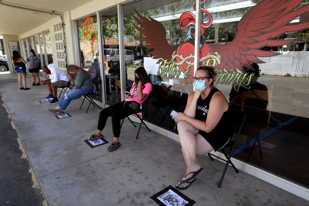 Customers wait in line for body piercings at Heart & Soul Tattoo in Yuba City.