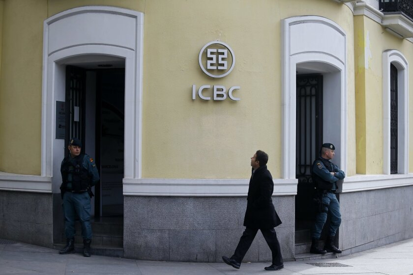 Spanish Civil Guard policemen stand guard outside China's ICBC bank offices, in Madrid, Spain, Wednesday, Feb. 17, 2016. Spanish police searched offices of China's ICBC bank in downtown Madrid and arrested five people Wednesday as part of a money laundering and tax fraud probe. (AP Photo/Francisco