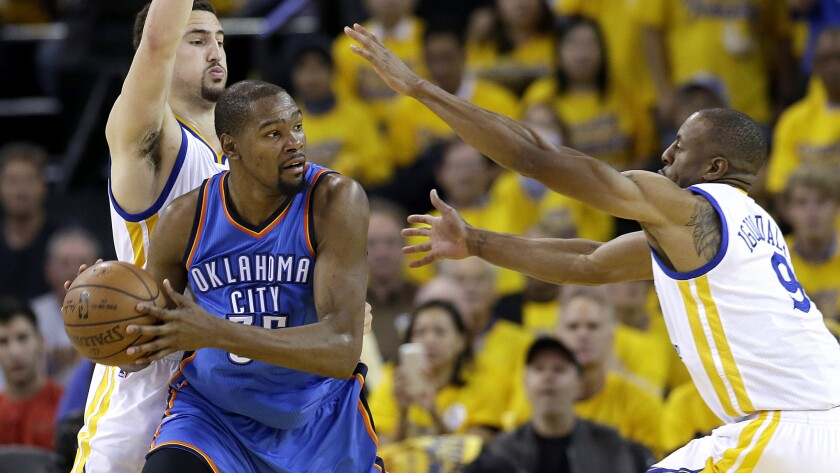 Kevin Durant is trapped by Warriors guard Klay Thompson and forward Andre Iguodala (9) during Game 2 of their playoff series in May.