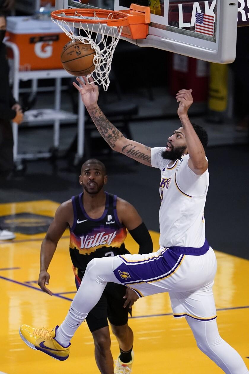 El jugador de los Lakers de Los Ángeles Anthony Davis, a la derecha, trata de atrapar un rebote junto al jugador de los Suns de Phoenix Chris Paul, en la primera mitad de su juego de NBA el domingo 9 de mayo de 2021 en Los Ángeles. (AP Foto/Marcio Jose Sanchez)