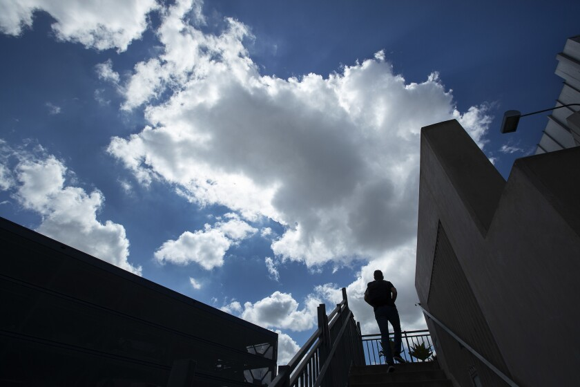 A man makes his way to the second story of a plumbing store in Los Angeles under partially cloudy skies.