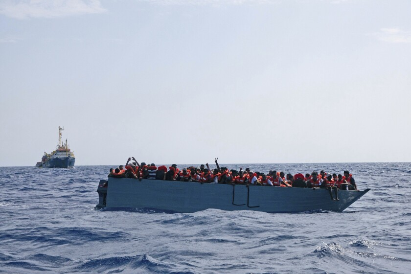 In this photo taken on Aug. 2, 2021 a boat overcrowded with migrants is waiting to be rescued by Sea Watch 3 in the Mediterranean sea. Italy on Wednesday, Aug. 4, 2021, pressed fellow EU nations to open their ports to migrants rescued by European humanitarian ships as political tensions grow in the Italian government over sharply rising number of arrivals this summer on the country's southern shores. (Sea-Watch.org via AP)