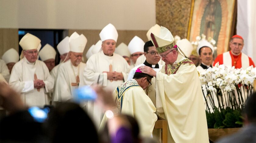 The Rev. Kevin Vann, bishop of Orange, lays his hands on the head of the Rev. Thomas Thanh Nguyen during Nguyen's ordination as auxiliary bishop in the diocese, home to an estimated 70,000 Vietnamese American Catholics.