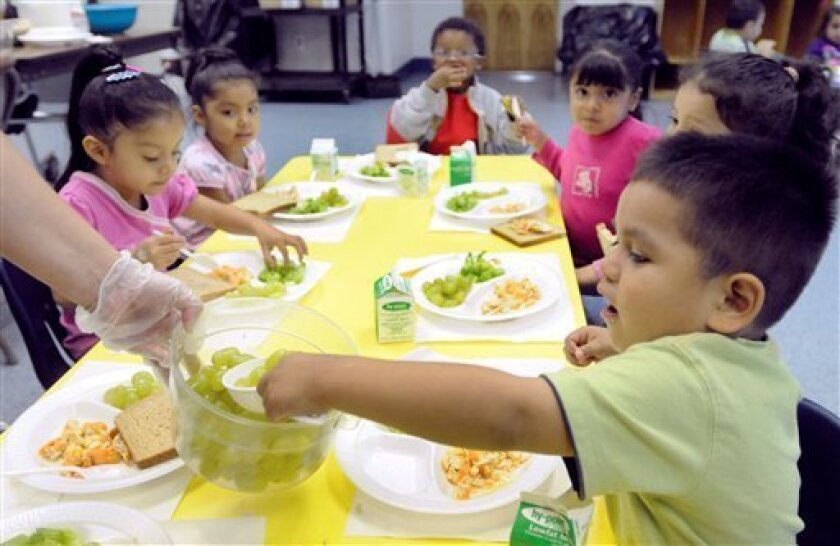 In this photograph taken Friday, Oct. 2, 2009, Jean Carlos Rubell, 3, helps himself to grapes during preschool lunch at the Latin American Community Center in Wilmington, Del. (AP Photo/ Steve Ruark)