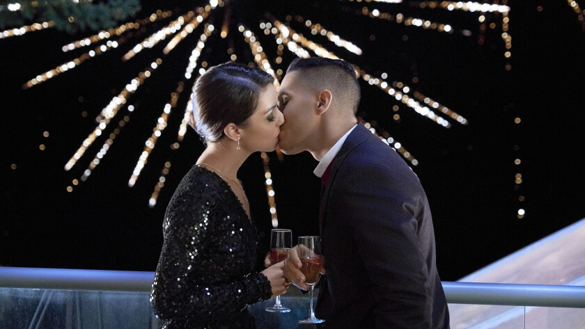 "Adelaide Kane and Carlos PenaVega in ""A Midnight Kiss"" on Hallmark."