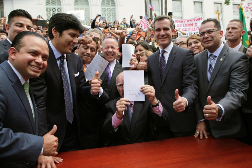 From left, Assemblyman Luis Alejo, state Sen. Ricardo Lara (partially visible), Sen. Kevin de León, Los Angeles City Councilman Gil Cedillo, Senate leader Darrell Steinberg, Mayor Eric Garcetti and Assemblyman V. Manuel Perez give a thumbs-up as Gov. Jerry Brown holds up a signed bill that will allow immigrants lacking legal immigration status to obtain California driver's licenses.