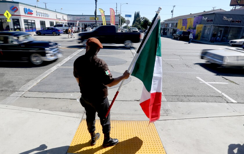 A man in brown beret robes holds a Mexican flag on the sidewalk as cars drive by on Whittier Boulevard