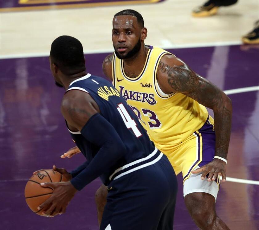 LeBron James (d) de los Lakers en acción ante Paul Millsap (i) de los Nuggets hoy, martes 2 de octubre de 2018, durante un partido de baloncesto de la NBA, entre los Denver Nuggets y Los Ángeles Lakers, en el Staples Center de Los Ángeles (EE.UU.). EFE