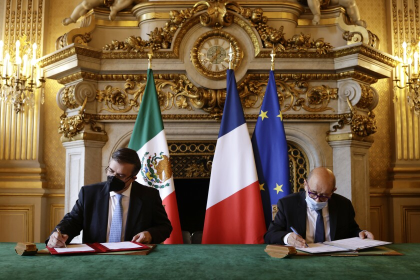 French Minister for Foreign Affairs Jean-Yves Le Drian, right, and Mexican Foreign Minister Marcelo Ebrard sign documents during their meeting in Paris, Thursday, July 1, 2021. France and Mexico signed an agreement Thursday on cooperating against the trafficking of cultural artifacts, a deal that the Mexican foreign minister called an important step toward recovering and protecting Mexico's cultural heritage. (Yoan Valat, Pool photo via AP)