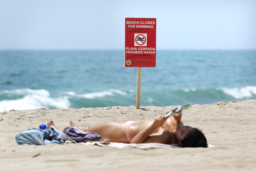 """A woman sunbathes near a """"Beach Closed for Swimming"""" sign."""