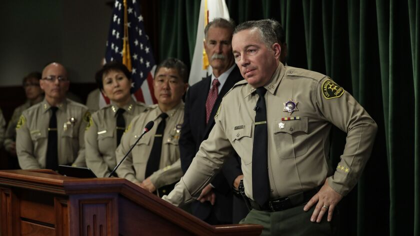 L.A. County Sheriff Alex Villanueva, shown at a Jan. 30 news conference, has defended his decision to rehire fired deputies.