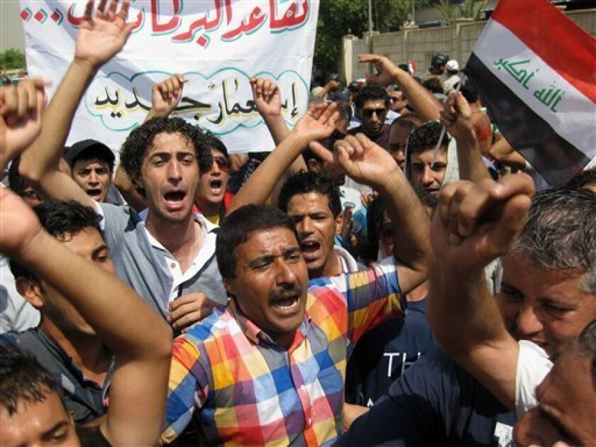 "Protesters chant slogans against the Iraqi parliament in Baghdad, Iraq, Saturday, Aug. 31, 2013. Protesters held rallies in Baghdad and the southern Iraqi city of Basra to demand to cancel parliamentarians' pensions. The Arabic on the banner reads, ""Parliamentarians' pensions in a new colonialism."""