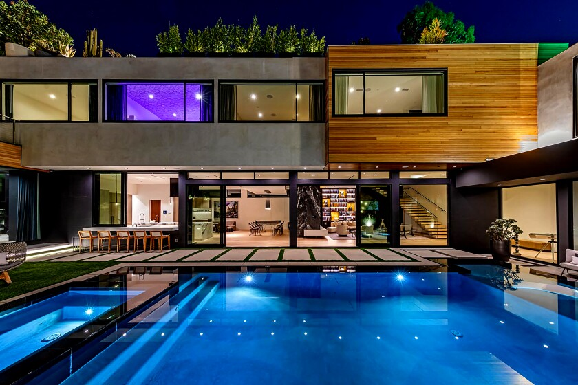 The contemporary showplace in the Hollywood Hills is setup for entertaining with walls of glass that open to a swimming pool and a rooftop deck with a spa. A fire feature encased in a wall of black marble draws the eyes in the living room, while a glass-enclosed wine cellar was built into the other side, which faces the dining room. Striking wallpaper, Venetian plaster walls and custom closets are among designer-done features of the home, listed for $11.5 million. The 6,487-square-foot home has six bedrooms and 6.5 bathrooms including a master suite with a private patio.