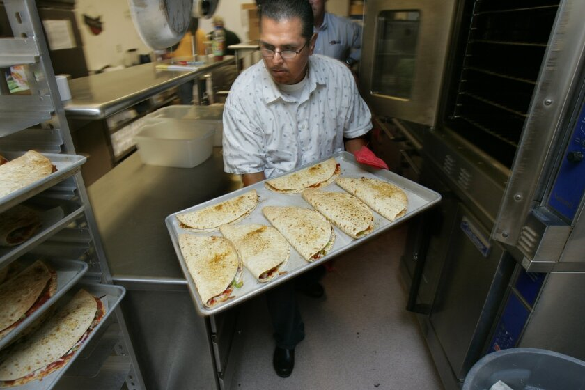 """Angel De La Vega removes chicken fajita quesadillas from the oven at a Sweetwater cafeteria. He has been placed on leave as part of an investigation into theft and nepotism. """"This is just allegations,"""" he said. (2008 file photo • U-T)"""