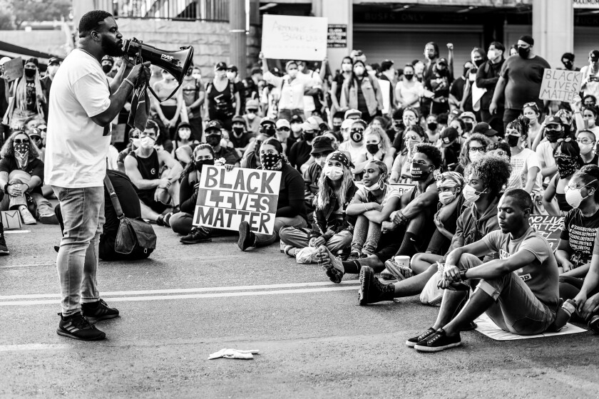 An unidentified Black man speaks to a seated crowd on Spring Street in downtown Los Angeles.