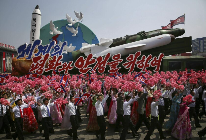 FILE - In this April 15, 2017, file photo, North Korean men and women wave flags and plastic flowers