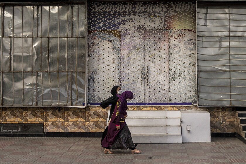 Afghan women walk past a closed beauty salon in Kabul on Saturday.